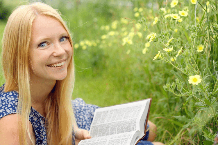 happy woman reading Bible in a field