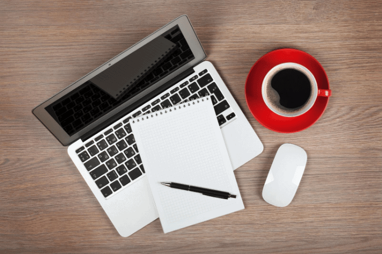 computer with notebook, pen and cup of coffee