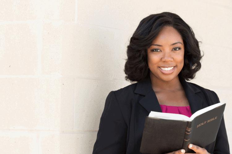 smiling woman reading a Bible