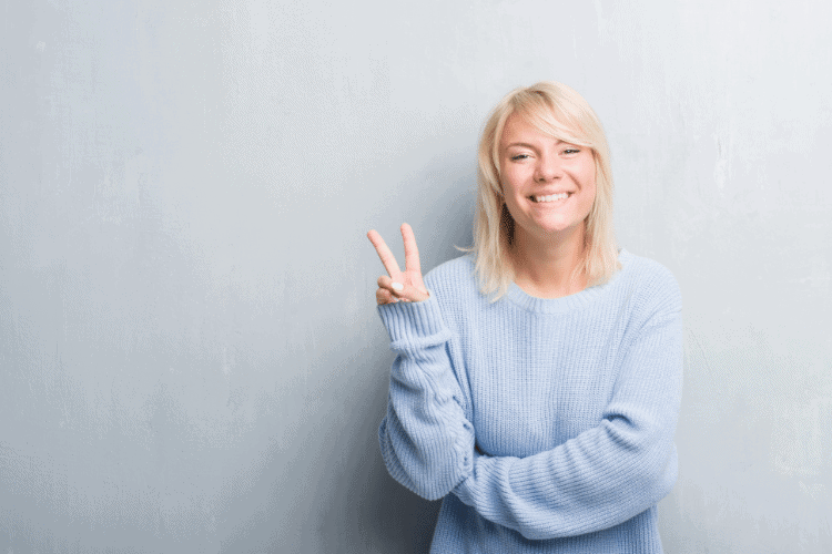 smiling woman holding up two fingers