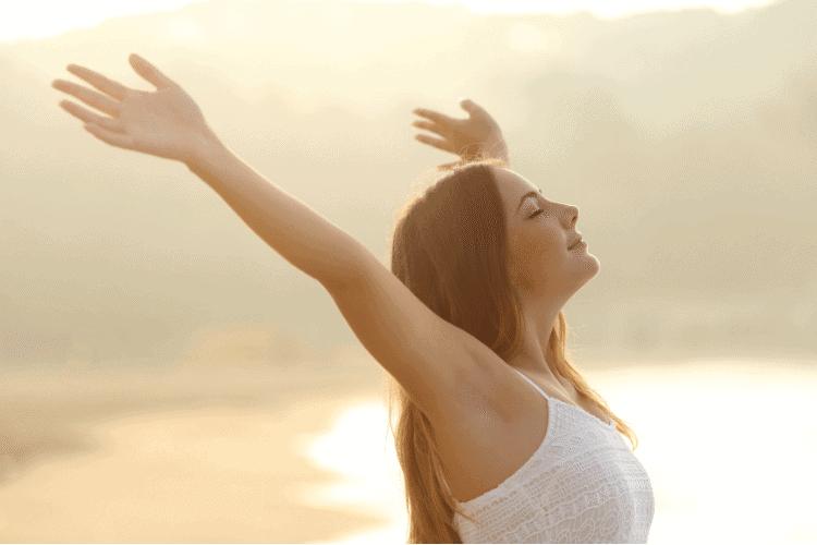 Woman raising arms on beach