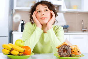 woman choosing fruit or a donut