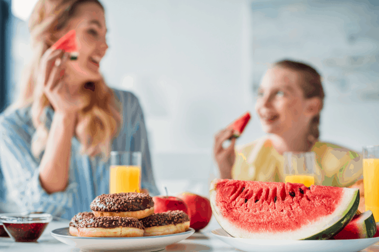 woman and girl and eating fruit instead of donuts