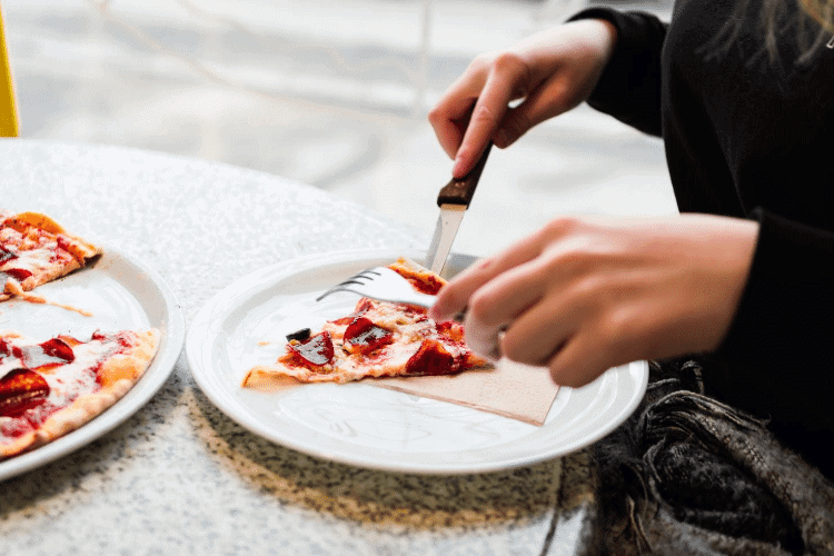 person eating pizza with a fork and knife