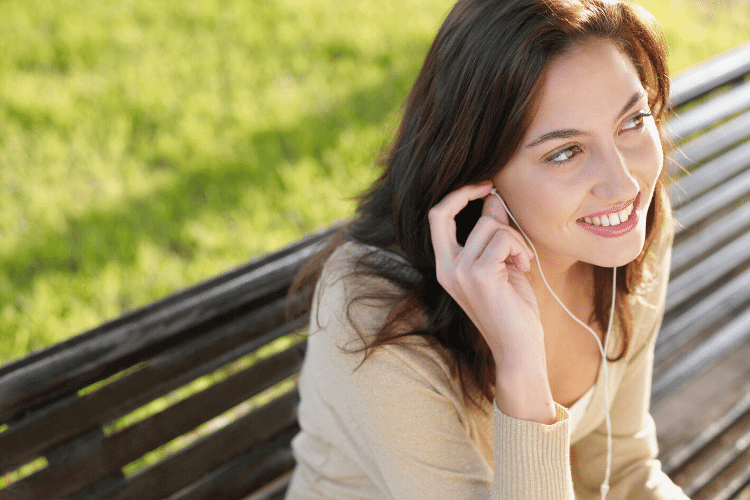 smiling woman listening on earbuds