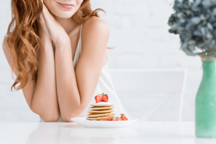 photo of woman looking at pancakes and strawberries on a plate