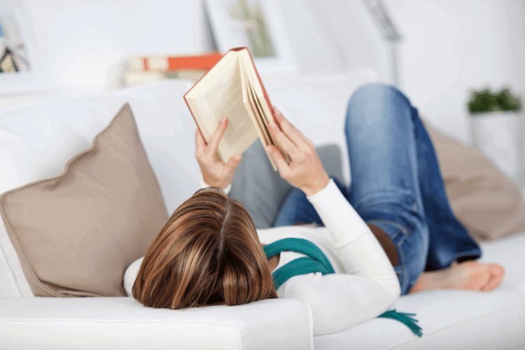 image of woman laying a couch reading a book