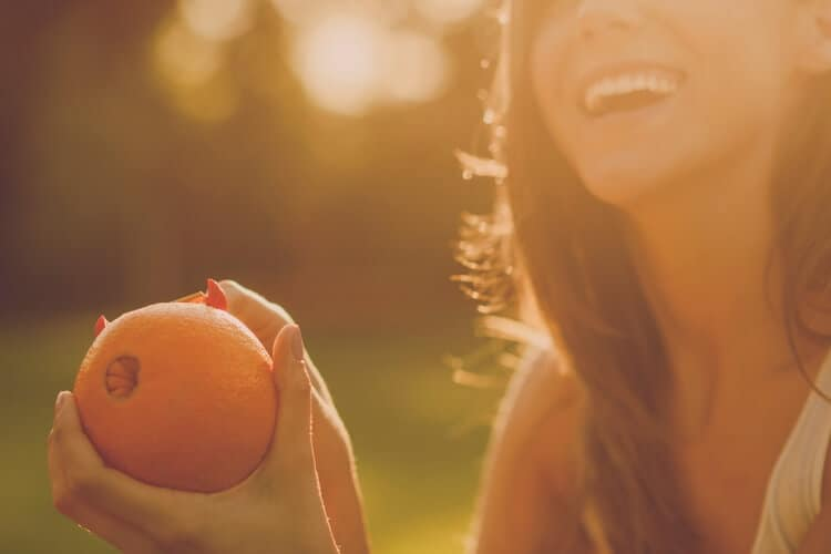 picture of woman eating orange