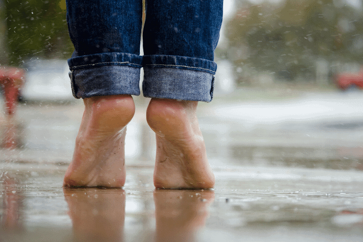 image of woman's bare feet standing in a puddle