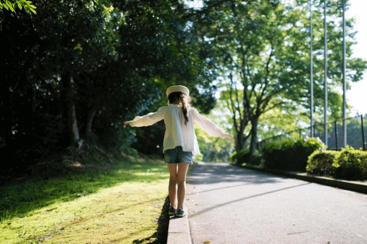 little girl balancing on curb