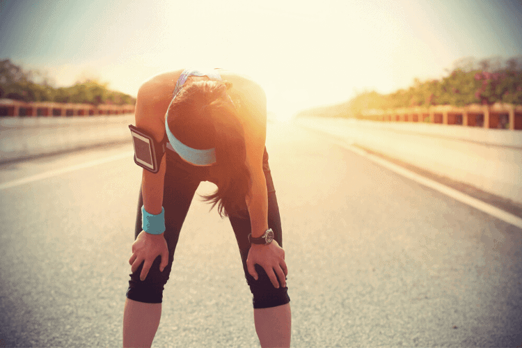woman standing in the road after running discouraged about exercise and body image