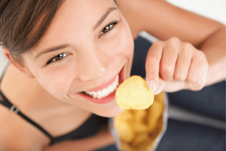 happy woman eating a potato chip